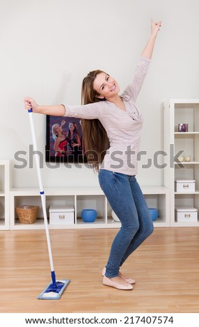 Portrait Of Young Woman Dancing In Home While Cleaning Floor - stock photo
