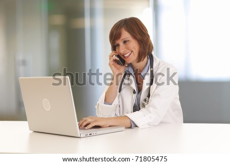Portrait of young woman doctor in white coat at computer using phone - stock photo