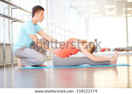 Portrait of young woman doing physical exercise with help of her trainer