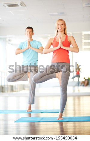 Portrait of young woman doing yoga exercise with guy on background - stock photo