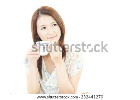 Portrait of young woman drinking cup of tea.