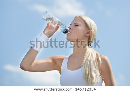 Portrait Of Young Woman Drinking Water After Jogging - stock photo