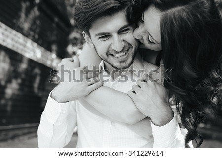 Portrait Of Young Woman Embracing Her Boyfriend From Behind - stock photo