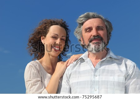 portrait of young woman embracing her father and smiling, blue sky