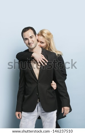 Portrait of young woman embracing man from behind against light blue background - stock photo