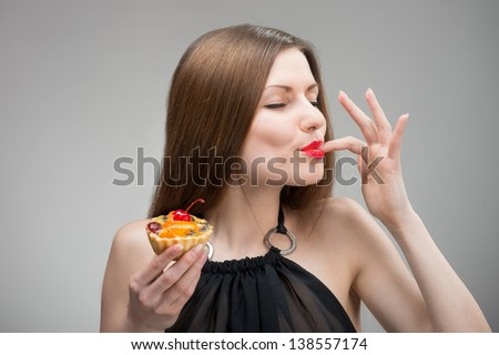 Portrait of young woman enjoying the cake - stock photo