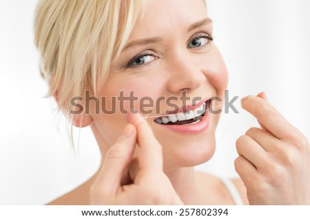 Portrait of young woman flosses her teeth with dental floss looking at camera
