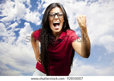portrait of young woman gesturing victory against a cloudy sky background