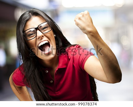portrait of young woman gesturing victory against a crowded place