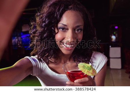 Portrait of young woman having a cocktail in bar