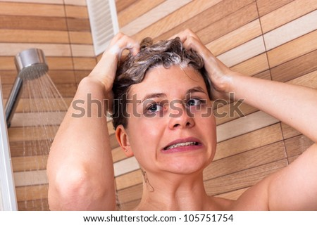 Portrait of young woman having cold shower - stock photo