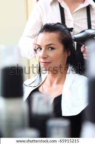 portrait of young woman having her hair being cut - stock photo