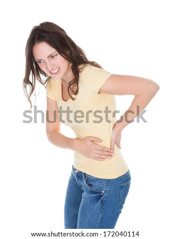 Portrait Of Young Woman Having Pain In Her Back Over White Background - stock photo