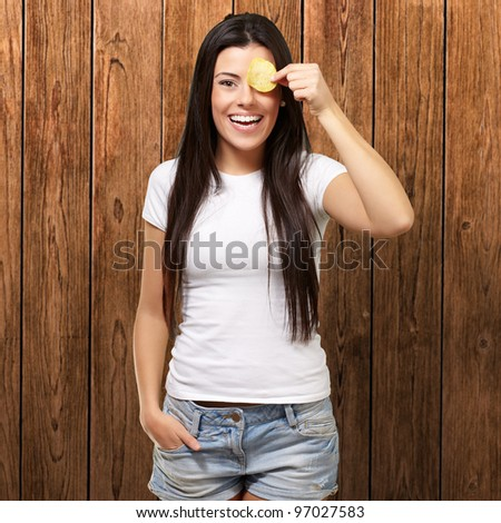 portrait of young woman holding a potato chip in front of her eye against a wooden wall