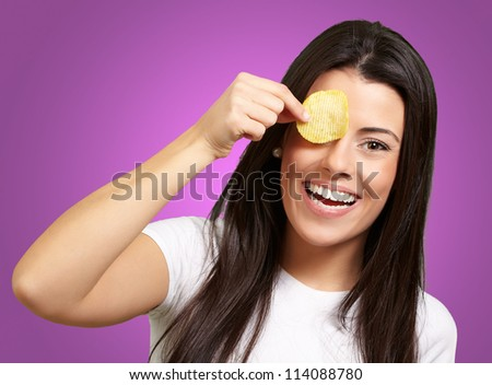 portrait of young woman holding a potato chip in front of her eye over purple - stock photo