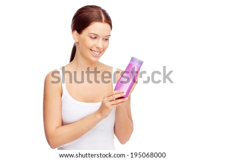 Portrait of young woman holding body lotion or shower gel and looking at it