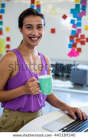Portrait of young woman holding coffee cup and using laptop in the office - stock photo