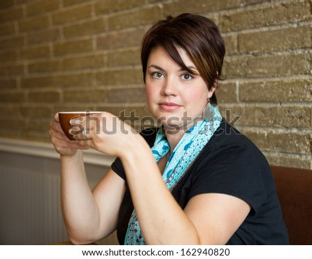 Portrait of young woman holding coffee cup in cafe - stock photo