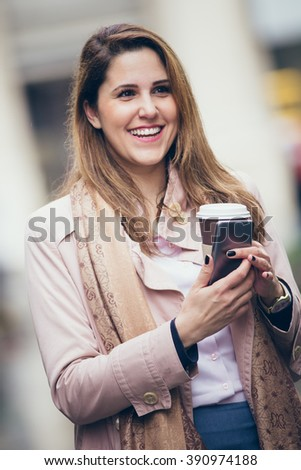 Portrait of young woman holding coffee to go and mobile phone