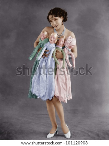 Portrait of young woman holding four dolls - stock photo
