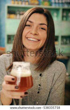 Portrait of young woman holding glass of beer
