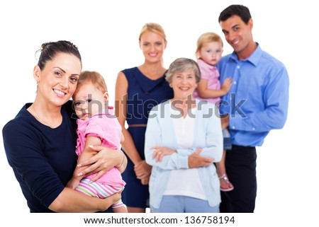 portrait of young woman holding her baby with extended family on background - stock photo