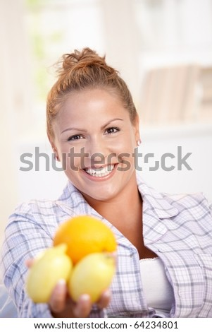 Portrait of young woman holding lemons in her hand smiling, living healthy.? - stock photo