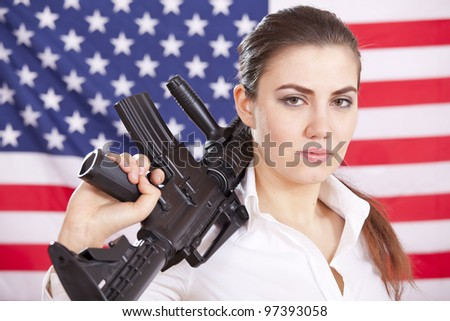 portrait of young woman holding machine gun over american flag - stock photo