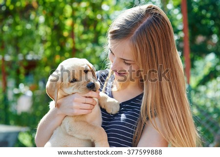 Portrait of Young woman holding on hands puppy Labrador. - stock photo