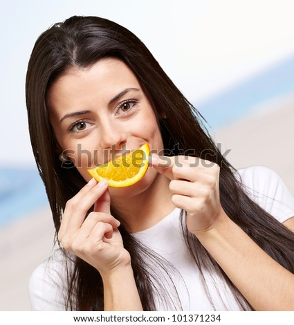 portrait of young woman holding orange slice against a beach