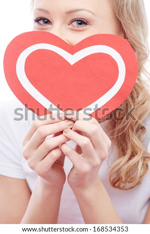 Portrait of young woman holding paper heart