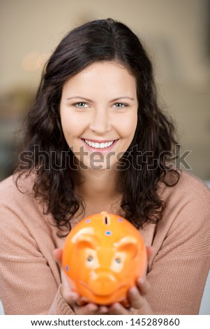 Portrait of young woman holding piggybank at home - stock photo