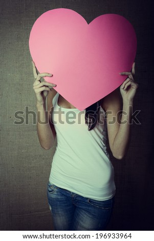 portrait of young woman holding pink heart incognito, love holiday valentine symbol over canvas background, toned - stock photo