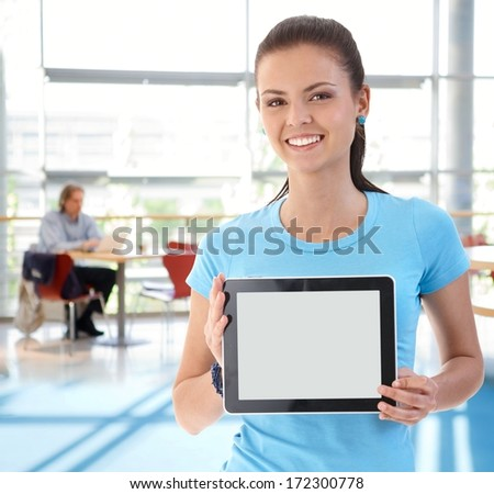 Portrait of young woman holding tablet computer, smiling, looking at camera. - stock photo