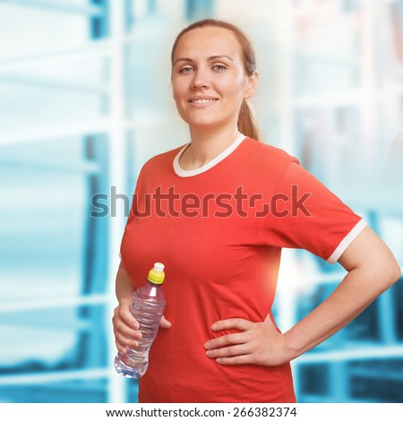 Portrait of young woman holding water bottle at gym