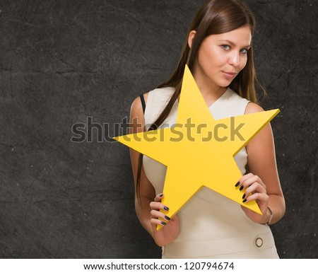 Portrait Of Young Woman Holding Yellow Star against a grunge wall - stock photo