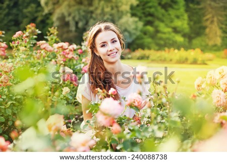 Portrait of young woman in a rose garden - stock photo