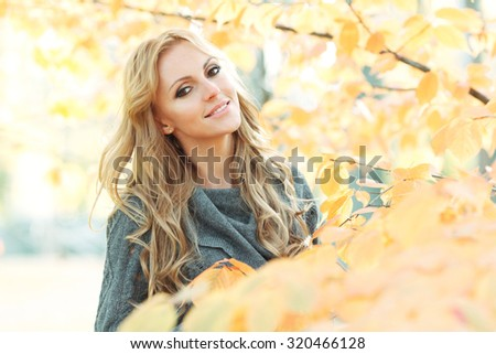 Portrait of young woman in beautiful autumn park - stock photo