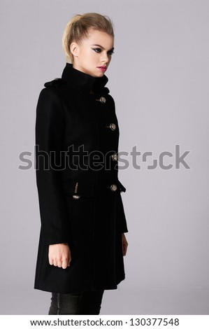portrait of young woman in coat posing on gray background - stock photo
