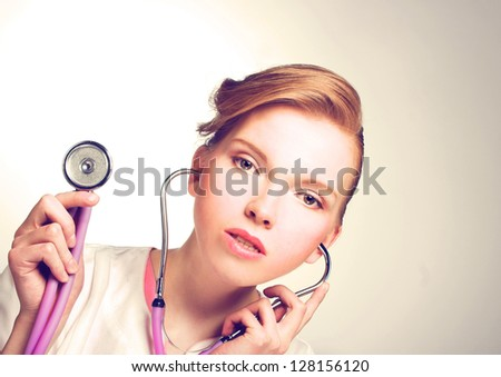 Portrait of young woman in doctor's smock and with stethoscope