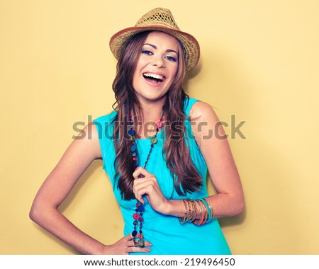 portrait of young woman in fashion style with long hair in blue dress standing against yellow background - stock photo