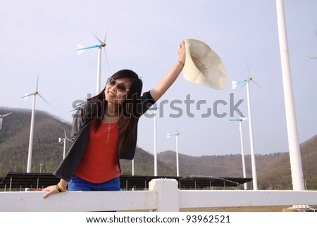 Portrait of young woman in front of windmill - stock photo