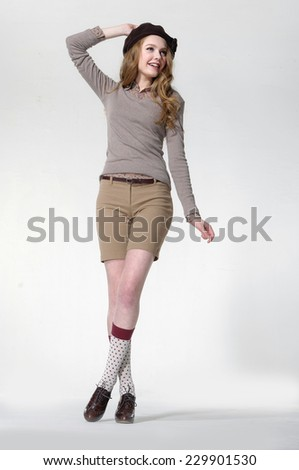 Portrait of young woman in hat standing full-length - stock photo