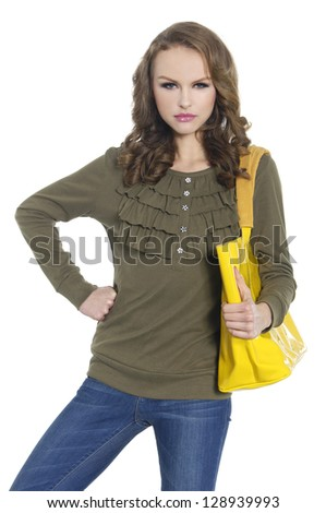 portrait of young woman in jeans with yellow bag posing
