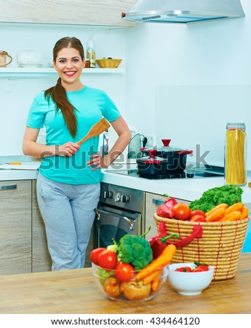 Portrait of young woman in kitchen. Cooking food at home.