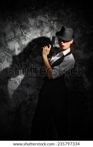 Portrait of young woman in manly style with gun at grey rough wall - stock photo