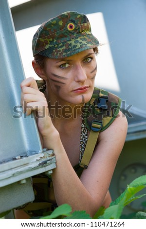 Portrait of young woman in military camouflage on the industrial background - stock photo