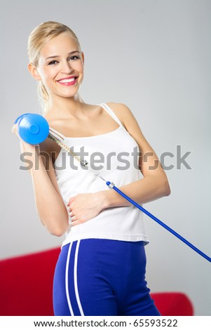 Portrait of young woman in sportswear, doing fitness exercise with dumbbell and expander at home - stock photo