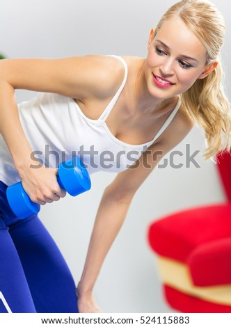 Portrait of young woman in sportswear, doing fitness exercise with dumbbell, indoors. Healthy lifestyle, weight lossing and sporting theme concept shot.