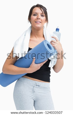 Portrait of young woman in sportswear holding water bottle and mat over white background
